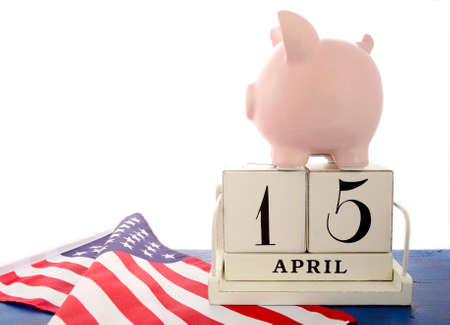 april 15: USA Tax Day, April 15, concept with piggy bank on top of calendar on flag on blue wood background.