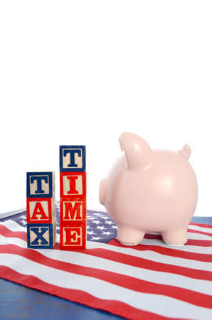 april 15: USA Tax Day, April 15, concept with piggy bank and blocks spelling Tax Time on flag on blue wood background, vertical with copy space.