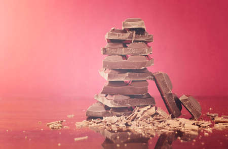 flare stack: Stack of chocolate on reflective glass against red background with applied retro vintage style filters and added light flare.