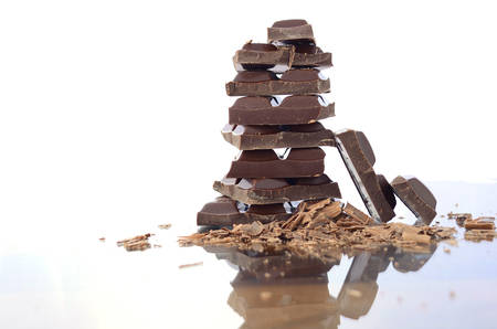 chocolate bars: Stack of chocolate on reflective glass against white background. Stock Photo