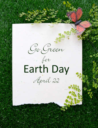 Earth Day, April 22, Concept with recycled paper in grass with fern and butterfly and text.