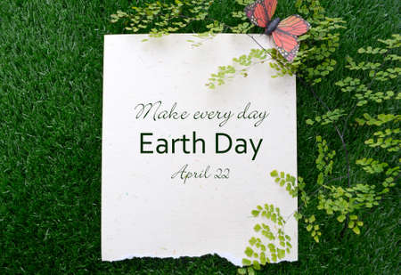 earth day: Earth Day, April 22, Concept with recycled paper in grass with fern and butterfly and text.