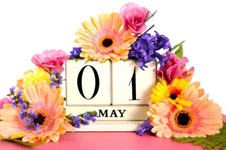 kalendarz: Szczęśliwy dzień maja kalendarz rocznika drewna ozdobiony wiosennych kwiatów na różowym tabeli drewna.
