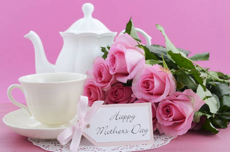 mothering: Happy Mothers Day Pink Roses and Tea Pot and tea setting on shabby chic style vintage distressed pink wood table. . Stock Photo