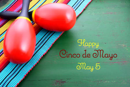 mayo: Happy Cinco de Mayo background with colorful maracas on Mexican theme dark green distressed table with copy space.
