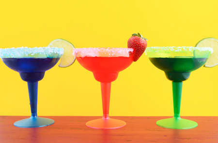 Happy Cinco de Mayo colorful party theme with bright color margarita drinks on red wood table and yellow background. Stock Photo
