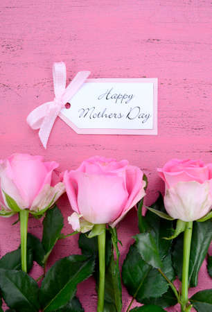 mothering: Happy Mothers Day Pink Roses on Vintage style distressed pink wood table with gift tag.