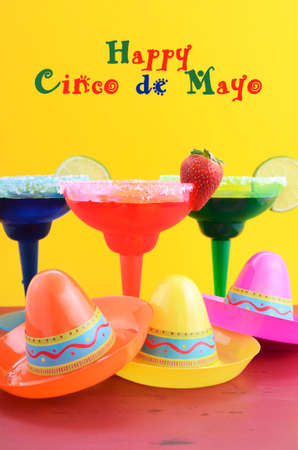 margarita: Happy Cinco de Mayo colorful party theme with bright color margarita drinks on red wood table and yellow background. Stock Photo