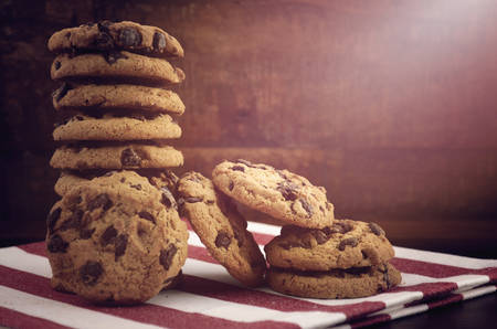 chocolate chip cookies: Stack of chocolate chip cookies on red and white stripe napkin against a dark wood background, with applied vintage style filters and added light stream. Stock Photo