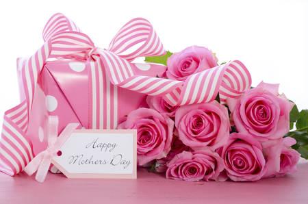 De gelukkige Dag van roze polka dot gift met roze en witte streep lint en cadeau-tag op vintage roze houten tafel.
