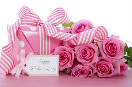 Happy Mothers Day pink polka dot gift with pink and white stripe ribbon and gift tag on vintage pink wood table. Imagens