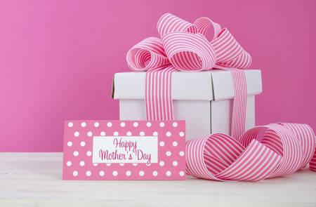 Feliz caja de regalo blanco Día de la Madre con la cinta raya rosada con el saludo etiqueta en rosa moderno y blanco de mesa de madera de época. Foto de archivo - 39046155