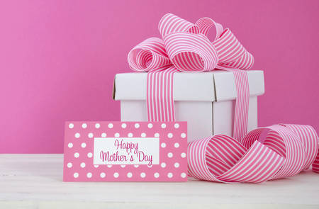 Happy Mothers Day white gift box with pink stripe ribbon with greeting tag  in modern pink and white vintage wood table. Stock Photo