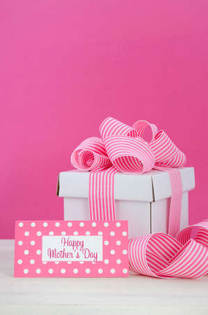 mothering: Happy Mothers Day white gift box with pink stripe ribbon with greeting tag  in modern pink and white vintage wood table. Stock Photo