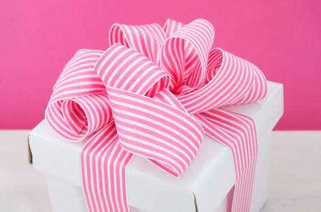 mothering: Happy Mothers Day white gift box with pink stripe ribbon in modern pink and white vintage wood table background.
