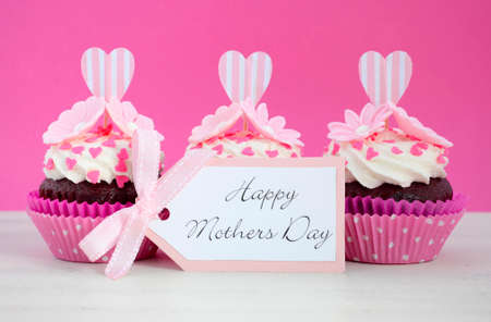 red velvet cupcake: Happy Mothers Day pink and white cupcakes with heart shape topper and hearts and flowers decorations on vintage white wood table.