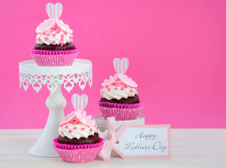 mothering: Happy Mothers Day pink and white cupcakes on retro style cake stands on vintage white wood table. Stock Photo