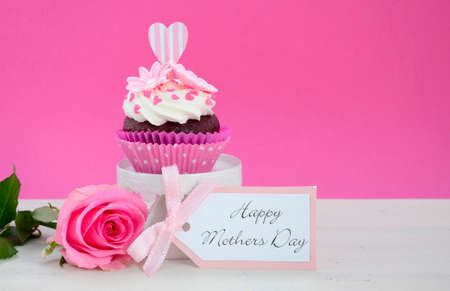 Happy Mothers Day pink and white cupcake on retro style cake stand and pink rose on vintage white wood table, with copy space. Stock Photo