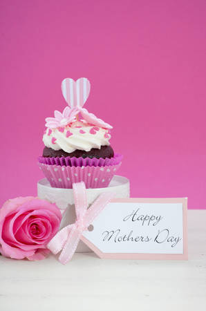mothering: Happy Mothers Day pink and white cupcake on retro style cake stand and pink rose on vintage white wood table, with copy space. Stock Photo