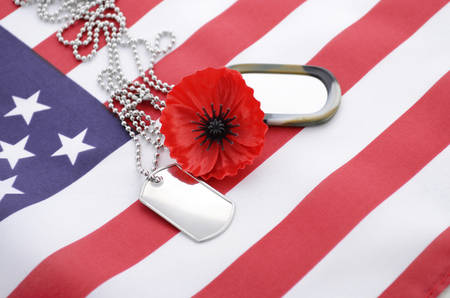 remembrance day poppy: USA Memorial Day concept with dog tags and red remembrance poppy on American stars and stripes flag. Stock Photo