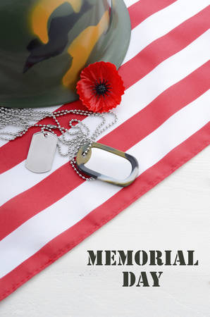 USA Memorial Day concept with dog tags and red remembrance poppy on American stars and stripes flag on white vintage wood table with title text.