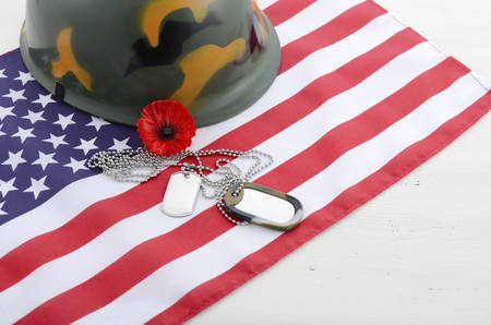 USA Memorial Day concept with dog tags and red remembrance poppy on American stars and stripes flag on white vintage wood table with copy space. photo