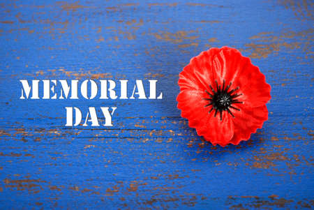 USA Memorial Day concept of red remembrance poppy on dark blue vintage distressed wood table, with title text.
