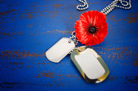 USA Memorial Day concept of red remembrance poppy on dark blue vintage distressed wood table, with soldiers dog tags.