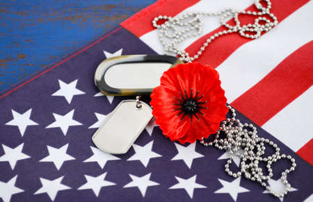 USA Memorial Day concept with dog tags and red remembrance poppy on American stars and stripes flag on dark blue vintage wood table.