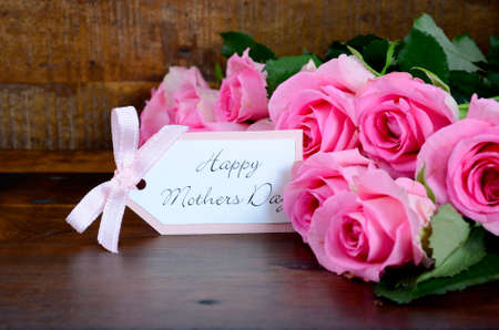 the mother: Happy Mothers Day fresh pink roses on dark wood distressed table and background, with gift tag.