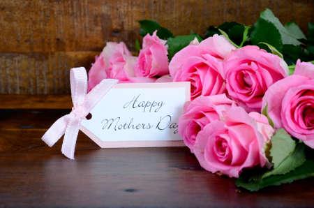 madre: Happy Mothers Day rosas de color rosa fresca en madera oscura mesa de angustia y de fondo, con etiqueta de regalo.