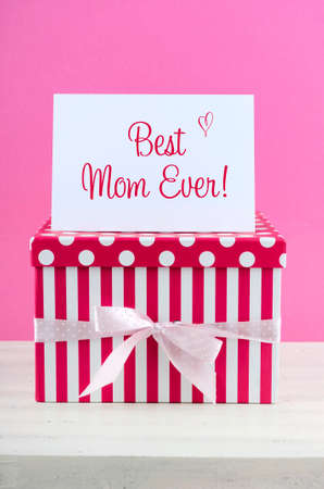 mothering: Happy Mothers Day pink and white gift with Best Mom Ever greeting card, on white shabby chic distressed wood table.
