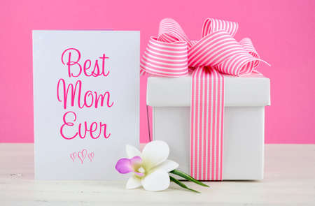 Happy Mothers Day pink and white gift with Best Mom Ever greeting card, on white shabby chic distressed wood table.