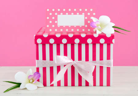 mothering: Happy Mothers Day pink and white gift with greeting card, on white shabby chic distressed wood table.