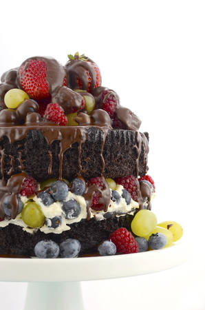 deliciously: Deliciously divine chocolate cake with strawberries, blueberries, raspberries and grapes, and cream on pale blue shabby chic table.