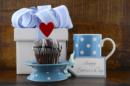 Happy Fathers Concept with blue and white gift, blue coffee mug, and cupcake on dark wood rustic background. Stock Photo