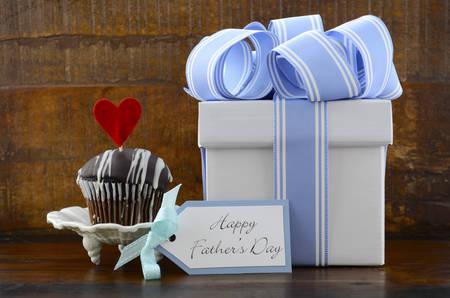 与蓝色和白色礼物和杯形蛋糕的愉快的父亲概念在黑暗的木土气背景。