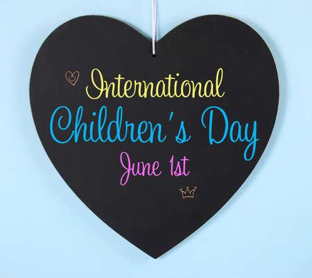 observance: International Childrens Day message greeting on heart shape blackboard sign on pale blue background.