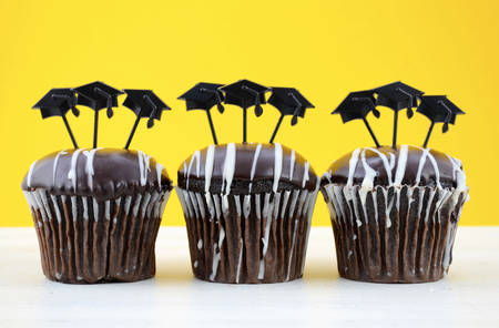 topper: Happy Graduation Day party chocolate cupcakes with graduation cap hat topper decorations, in yellow, black and white party theme.