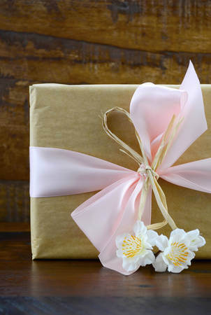 pink satin: Retro style natural kraft paper gift with pink satin ribbon and spring blossom flowers on dark wood table background. Stock Photo