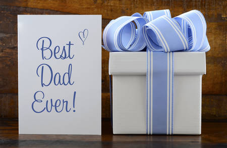 traditional gifts: Happy Fathers Gift with blue and white gift on wood background, and Best Dad Ever greeting card.
