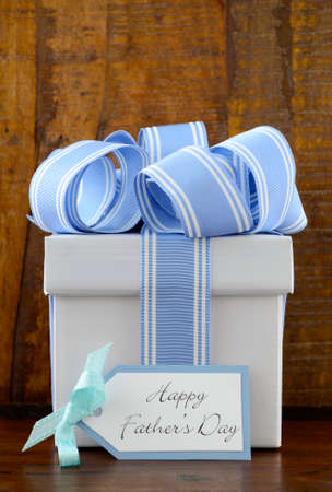 Happy Fathers Gift with blue and white gift on wood background, and greeting tag.