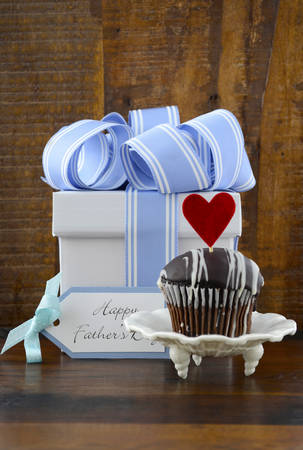 Happy Fathers Concept with blue and white gift and cupcake on dark wood rustic background.