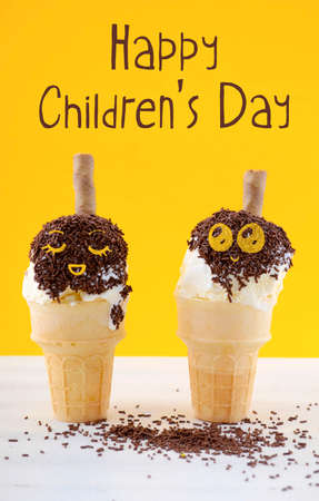 childrens food: Happy Childrens Day concept with fun ice cream cones with chocolate sprinkles on white shabby chic table and yellow background, with applied cute faces and text.