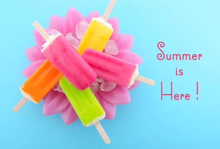 gelati: Summer is Here concept with bright color ice pop, ice creams on ice in pretty pink bowl blue background with text. Stock Photo