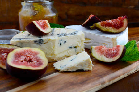 cheeseboard: Fresh figs on wooden cutting chopping board with jar of fig jelly preserve and gourmet cheese on dark wood rustic table background, close up.