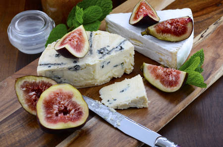 cheeseboard: Fresh figs on wooden cutting chopping board with jar of fig jelly preserve and gourmet cheese on dark wood rustic table background.