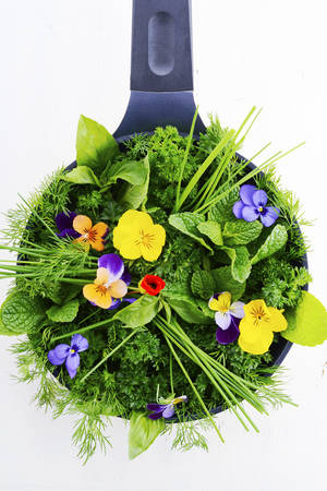 skillet: Cooking with herbs concept with fresh herbs and edible flowers in modern yellow fry pan skillet on white wood table.