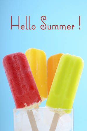 gelati: Summer is Here concept with bright color ice pop, ice creams on blue background and Hello Summer text. Stock Photo