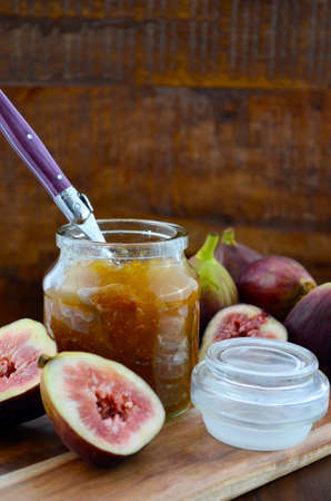 purple fig: Fresh figs on wooden cutting chopping board with jar of fig jelly preserve on dark wood rustic table background.